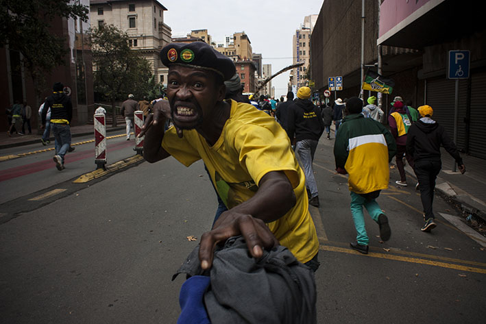 An ANC supporter postures for the camera near Beyers Naude Square in downtown Johannesburg. About 1000 ANC members gathered to show their support for the ANC and Zuma-led government as marches around the country, including a few blocks away in Mary Fitzgerald Square, called for President Zuma to step down following the firing of Finance Minister Pravin Gordhan and a massive midnight Cabinet reshuffle on the 31st of March. 7 April, 2017. Photo: Steve Kretzmann
