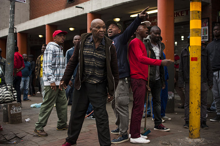 Taxi bosses and shop owners from the Bree Street taxi rank in downtown Johannesburg threaten retreating ANC members who had toyi-toyied down Sauer Street from their Luthuli House headquarters and tried to storm the taxi rank in search of alleged Nigerian drug dealers. Their attempt was scuttled when taxi bosses and vendors pushed back. 7 April 2017. Photo: Steve Kretzmann