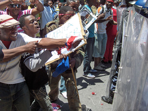 DRC nationals rip the French flag as riot police prevent them from reaching the French Consulate in Cape Town yesterday. (subs: Tues) Photo: Peter Luhanga/WCN