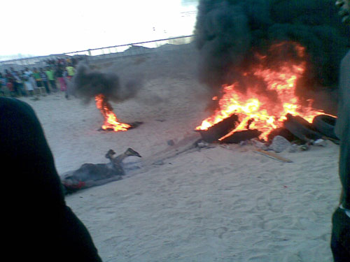 One of three men set alight in vigilante action in Enkanini, Khayelitsha on Monday evening manage to crawl out of a pile of burning tyres, but died later of his injuries while in hospital. Photo: Nombulelo Damba/WCN