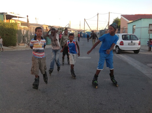 Juwaydin Kiewiets, 12, (on left) and his 'crew' rollerblade through the streets of Du Noon while many of their peers smoke tik. Photo: Peter Luhanga/WCN
