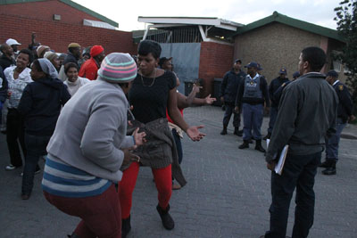About 100 residents of Site B, Khayelitsha, danced and sang outside the Khayelitsha police station on Tuesday evening to demand the release of a neighbourhood watch member who had been arrested following an alleged assault on two suspects on Sunday. Photo: Nombulelo Damba/WCN