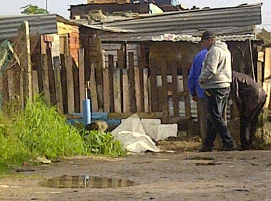 Residents of Kanana informal settlement in Gugulethu look at the body of a suspected thief who was stoned to death on Sunday night. Police only came to the scene at about 7am yesterday (subs: Mon). Photo: Nombulelo Damba/WCN