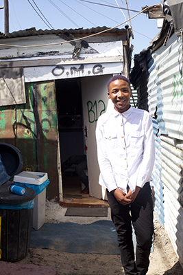 Orphaned teen Sinoxolo Cotyi outside his aunt's rickety zinc shack in Kwa 5 squatter camp, he beat all odds stacked against him to scoop seven distinctions in his 2015 matric results. Photo: WCN/Peter Luhanga.