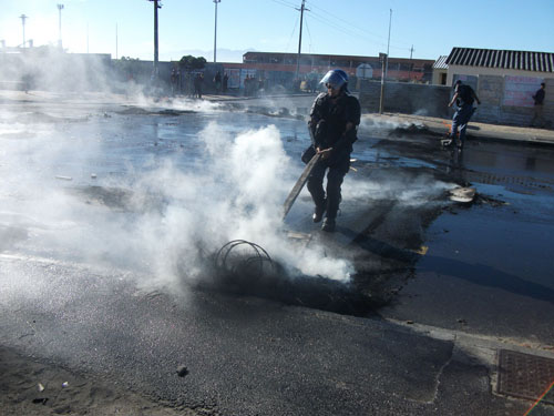 Police clear up following housing protests in Site B, Khayelitsha yesterday (subs: Tues) in which a water cannon had to be used to disperse a crowd of about 200 protestors. Photo: Nombulelo Damba/WCN