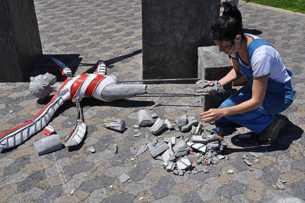 Sculptor Marieke Prinsloo-Rowe picks up the pieces of her artwork on the Seapoint promenade after one of her series of 18 works was vandalised this week. Photo: WCN