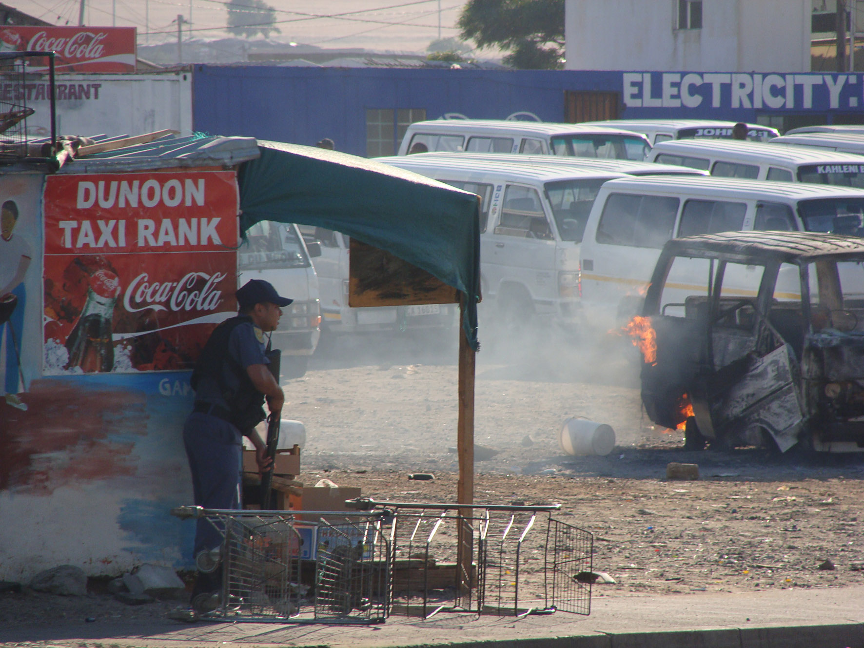 A policeman takes cover behind a food stall as a taxi burns at the Du Noon taxi rank. Photo: Peter Luhanga/WCN