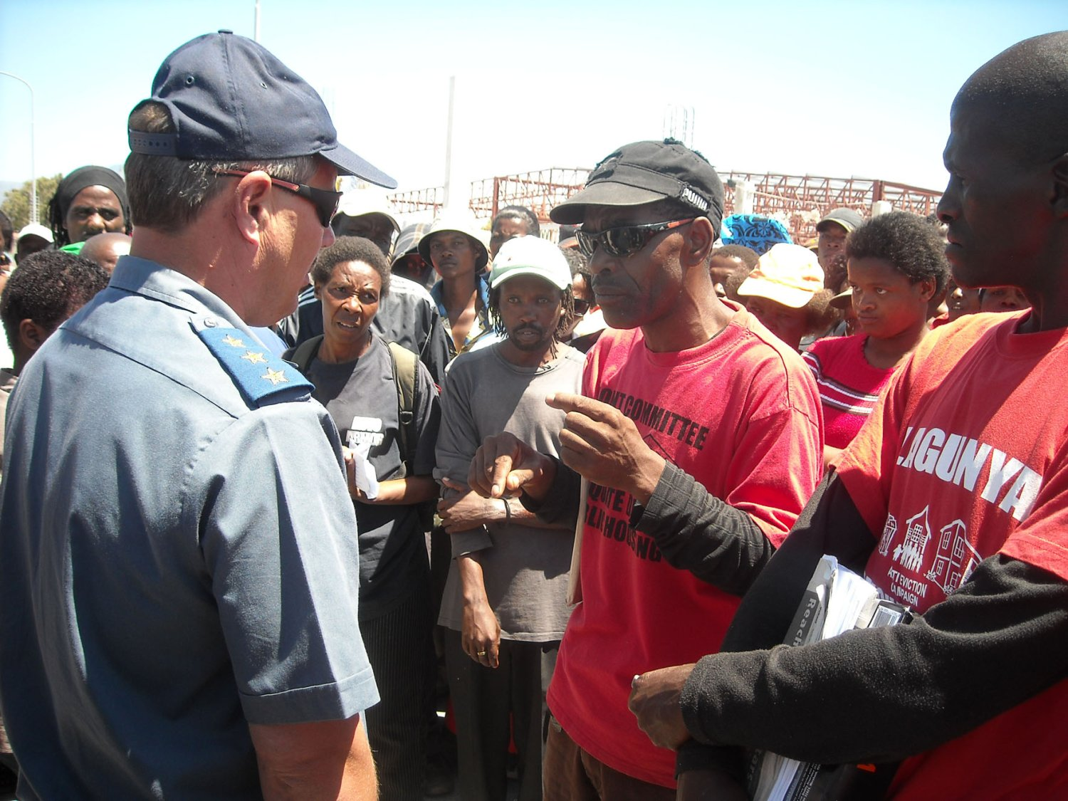 Leader of the Gugulethu Anti-Eviction Campaign, Mcendisi Thwala (centre) negotiates with a policeman who stopped over 2000 people from entering a construction site. The Anti-Eviction Campaign was demanded that jobs at the site be given to local residents. Photo: Peter Luhanga/WCN