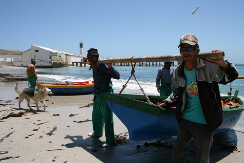 Fishermen carry their boat in from the sea in Doring Bay, 350km North of Cape Town. The fishing community has received R3million from the DTI to establish co-operatives. Photo: Patrick Burnett/WCN