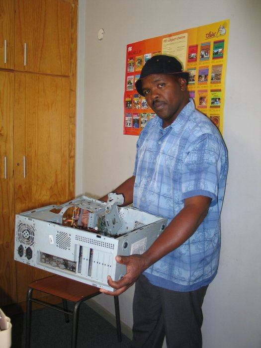School2.jpg: Usasazo Senior Secondary School caretaker Zakhele Silwanyana with a computer that has had the hard drive ripped out of it by vandals over school holidays. Photo: Sandiso Phaliso/West Cape News